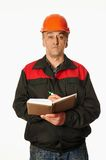 Worker in a orange hardhat writes in a notebook. Isolated on white Stock Image