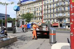 Worker in an orange uniform empties a trash can into the garbage truck. Vienna, Austria royalty free stock image