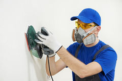 Worker with orbital sander at wall filling. Home improvement worker in protective mask and glasses working with sander for smoothing wall surface Stock Images