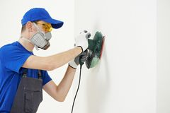 Worker with orbital sander at wall filling. Home improvement worker in protective mask and glasses working with sander for smoothing wall surface Royalty Free Stock Photos