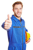 Worker in overall holding thumbs up Stock Photo