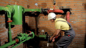 The worker in the overalls closes the water valve. The man turns off the heating in the boiler room. FullHD stock footage