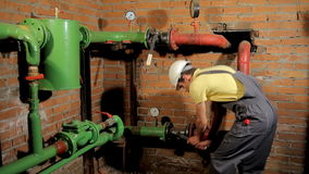 The worker in the overalls closes the water valve. The man turns off the heating in the boiler room. FullHD stock video footage
