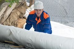 A worker in overalls covers stones and iron mesh with white wrap. A worker in overalls covers stones  and iron mesh with white wrap stock photo