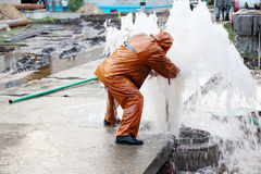Worker eliminates breakthrough of sewerage systems. Worker in overalls eliminates breakthrough of sewerage systems stock photo