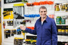 Worker In Overalls Gesturing In Hardware Store. Portrait of smiling worker in overalls gesturing in hardware store Royalty Free Stock Images