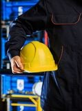 Worker with his helmet. Worker in overalls with his helmet in hand royalty free stock photo