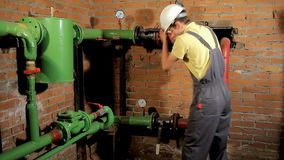 A worker in overalls opens the water valve. The man includes heating in the boiler room. FullHD stock video footage