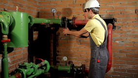 A worker in overalls opens the water valve. The man includes heating in the boiler room. FullHD stock footage