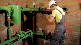 A worker in overalls opens the water valve. The man includes heating in the boiler room. FullHD stock video