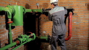 A worker in overalls opens the water valve. plumber comes and opens the valve. The man includes heating in the boiler. A worker in overalls opens the water valve stock video