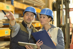 Worker with overseer controling stock. In warehouse Royalty Free Stock Photo