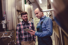 Worker and owner discussing over digital tablet at brewery Stock Image
