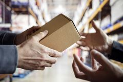 Worker with package in a distribution warehouse. Worker giving a package in distribution warehouse royalty free stock image