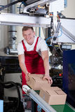 Worker packing boxes on conveyor belt Royalty Free Stock Images