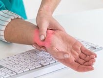worker with pain on the wrist by  hard work at office Royalty Free Stock Images
