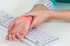 worker with pain on the wrist by  hard work at office Royalty Free Stock Image