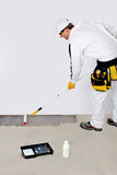 Worker paint with primer concrete. Construction worker with roller paints primer on concrete floor for waterproofing and protection Stock Photos