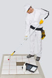 Worker paint primer tiles floor roller. Worker paint with primer on white bottle old white tiles on floor with roller before gluing new tiles Royalty Free Stock Images