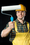 Worker with  paint roller. Male worker holding paint roller and smiling on black Stock Photo