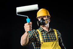 Worker with paint roller. Male worker in protective mask holding paint roller on black Royalty Free Stock Image