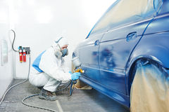 Worker painting auto car body Royalty Free Stock Image
