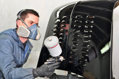 Worker painting black car. Stock Image