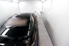 Worker painting a black car in a special booth Stock Images