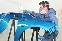 Worker painting blue bumper. Royalty Free Stock Photography