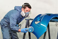 Worker painting blue bumper. Stock Image