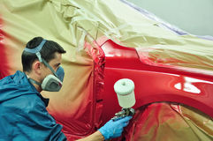 Worker painting a car. Royalty Free Stock Image