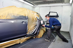 Worker painting a car. Royalty Free Stock Photo