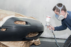 Worker painting a car. Royalty Free Stock Photography