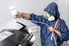 Worker painting a car black blank parts in special garage, wearing costume and protective gear Stock Photos