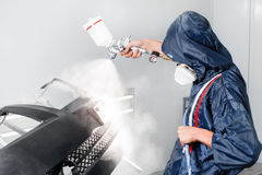 Worker painting a car black blank parts in special garage, wearing costume and protective gear Royalty Free Stock Image