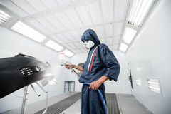 Worker painting a car black blank parts in special garage, wearing costume and protective gear Stock Photography