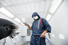 Worker painting a car black blank parts in special garage, wearing costume and protective gear Stock Image