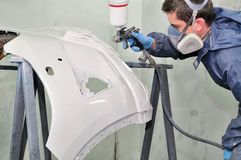 Worker painting a car bumper. royalty free stock photos
