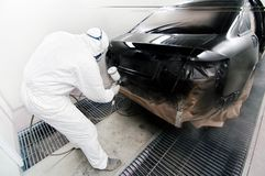 Worker painting a car in garage using an airbrush gun Royalty Free Stock Photography