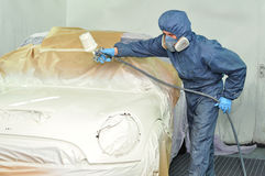 Worker painting car. Royalty Free Stock Photos