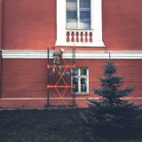 Worker painting facade of old building house, reconstruction and repair stock photography