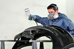 Worker painting a fender. Royalty Free Stock Images