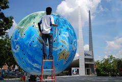 Worker painting the globe Stock Images