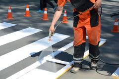 Worker is painting a pedestrian crosswalk. Technical road man worker painting and remarking pedestr. Ian crossing lines on asphalt surface using paint sprayer Royalty Free Stock Images