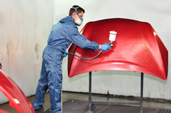 Worker painting a red bonnet. Professional car painter, painting red bonnet Stock Images