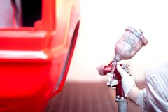 Worker painting a red car or element in garage Royalty Free Stock Image