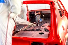 Worker painting a red car in a special garage Stock Images