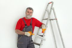 Worker painting  room to white. Worker painting wall to white and gesturing, with ladder and paint roller Stock Photography