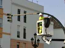 Worker painting semaphore. Workers uploaded to a platform, performs repairs and maintenance, painting a road sign or traffic light, on the public highway Royalty Free Stock Photography