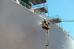 Worker painting of the ship. Worker painting ship hull using airbrush Royalty Free Stock Image